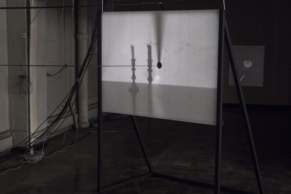 Four Shadows<br />looping 16mm film projection through punctured screen<br />2015-2016